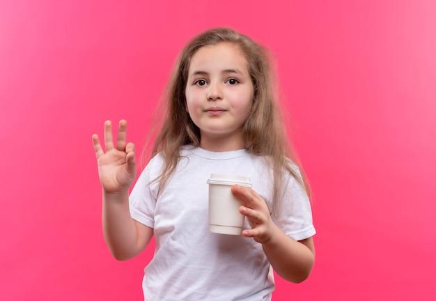Piccola ragazza della scuola che indossa la maglietta bianca che tiene la tazza di caffè che mostra okey gesto sulla parete rosa isolata
