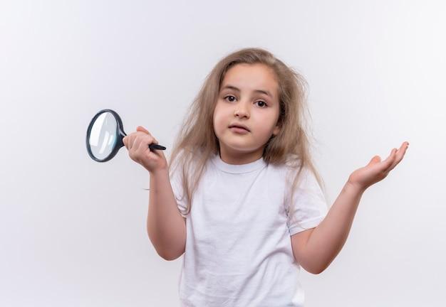 孤立した白い壁にどのようなジェスチャーを示す拡大鏡を保持している白いtシャツを着ている小さな女子高生
