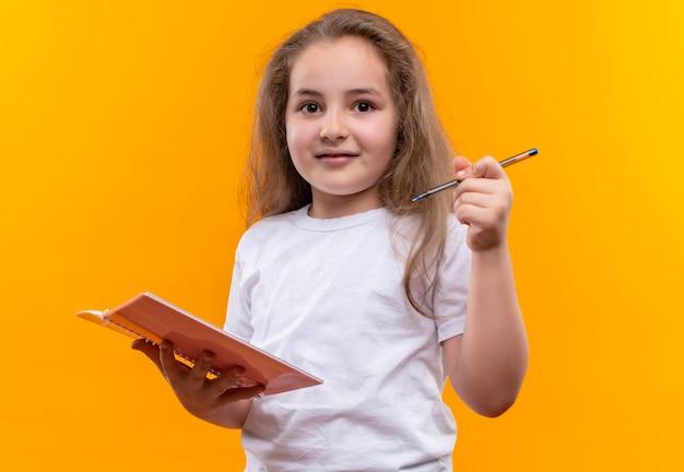 Маленькая школьница в белой футболке держит блокнот и ручку на изолированной оранжевой стене