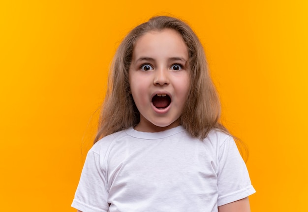 격리 된 오렌지 벽에 흰색 티셔츠 여는 입을 입고 어린 여고생