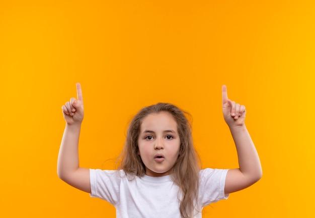 Маленькая школьница в белой футболке положила палец на изолированную оранжевую стену