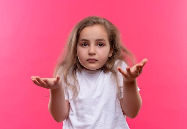 Piccola ragazza della scuola che indossa la maglietta bianca che mostra quale gesto sul muro rosa isolato
