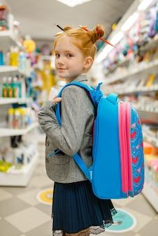 文房具店でバックパックを持った小さな女子高生。店で事務用品を買う女児、スーパーで小学生
