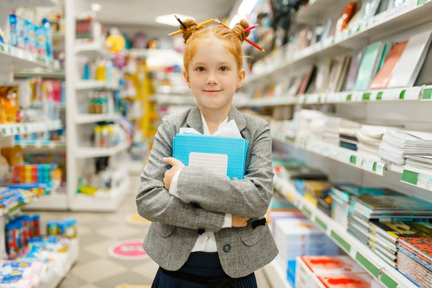 文房具店でノートを持つ小さな女子高生。店で事務用品を買う女児、スーパーで小学生