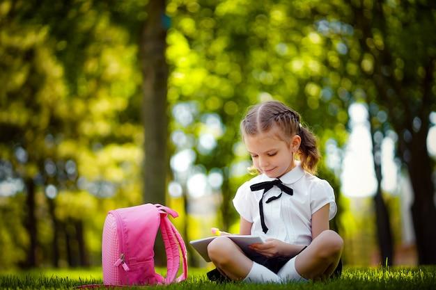 Маленькая школьница при розовый рюкзак сидя на траве после уроков и прочитанных уроков книги или исследования, думая идей, образования и концепции учить.