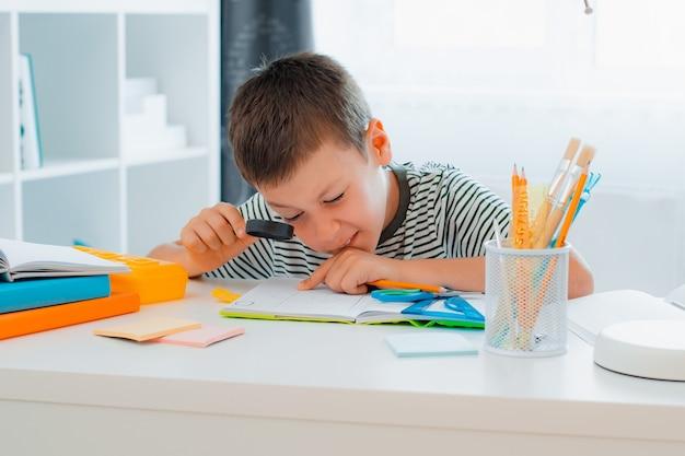 어린 남학생이 집에 있는 탁자에 앉아 돋보기를 통해 숙제를 하고 있습니다. 학교, 준비, 홈 스쿨링으로 돌아가기. 프리미엄 사진