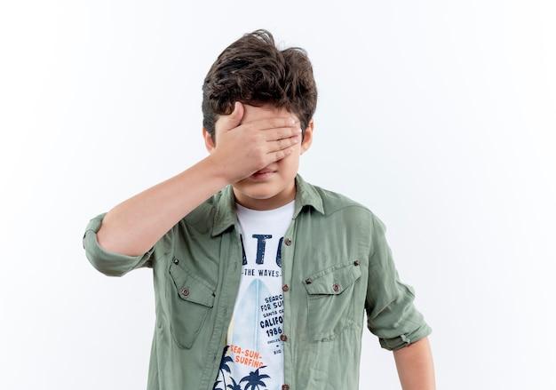 小さな男子生徒は白い背景で隔離の手で目を覆った 無料写真