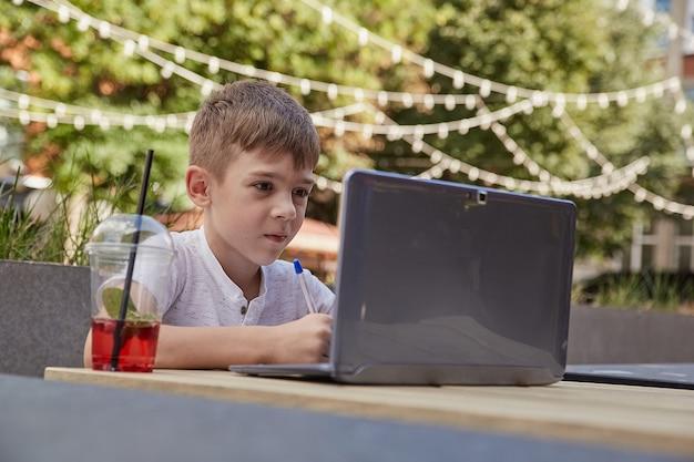 Маленький школьник делает домашнее задание на открытом воздухе с ноутбуком, делая заметки в тетради