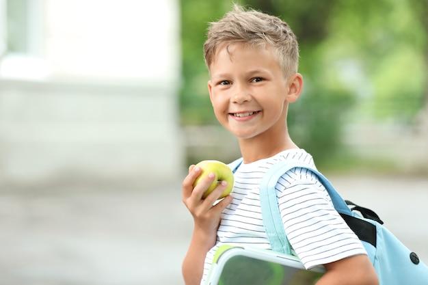 Маленький школьник ест вкусный обед на открытом воздухе