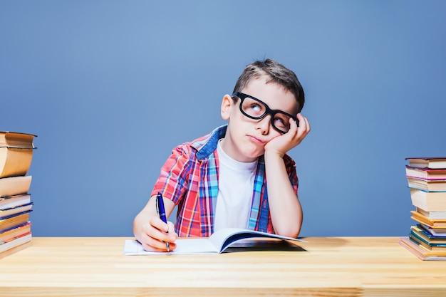 小さな男子生徒は教室の机で宿題を学びます。眼鏡の瞳孔は知識を得る