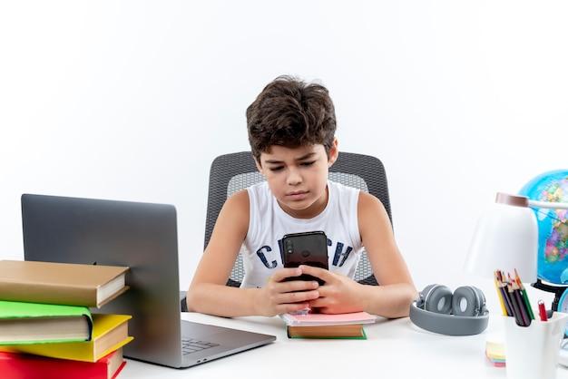 Piccolo scolaro seduto alla scrivania con strumenti di scuola tenendo e guardando il telefono