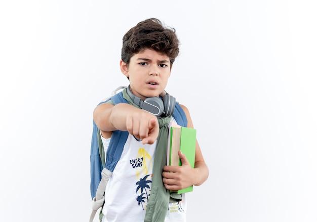 正面に本とポイントを保持しているバックパックとヘッドフォンを身に着けている小さな男子生徒