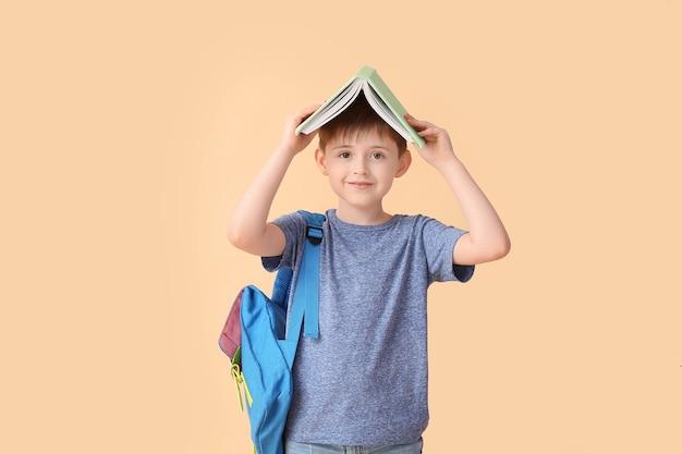 色の表面に本を持つ小さな男子生徒