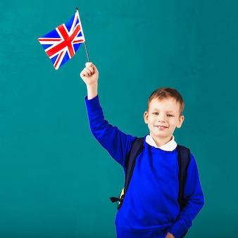 Маленький школьник с национальным флагом соединенного королевства. концепция школы. обратно в школу