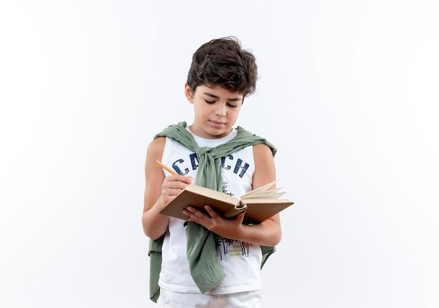 Piccolo scolaro che scrive qualcosa sul libro