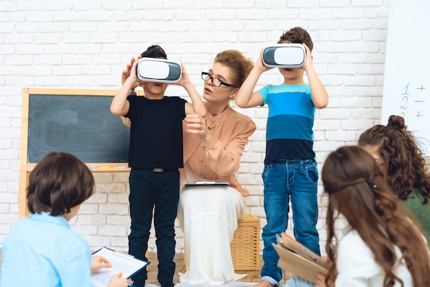 Little schoolchildren get acquainted with technology of virtual reality.