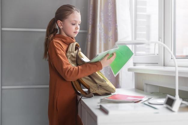 Little schoolgirl collecting books in a school bag