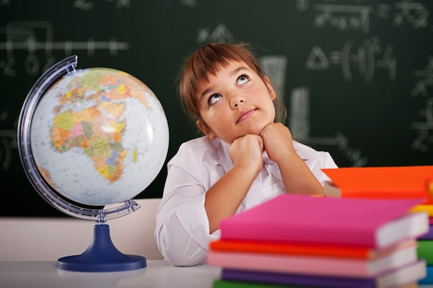 Little schoolgirl dreaming in classroom