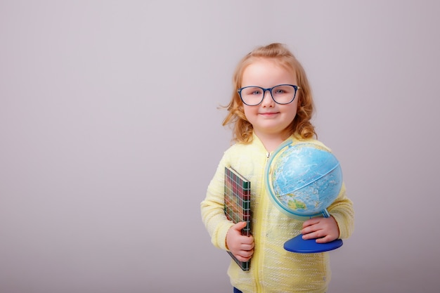 Little schoolgirl girl blonde in glasses with a globe in her hand shows emotions happines