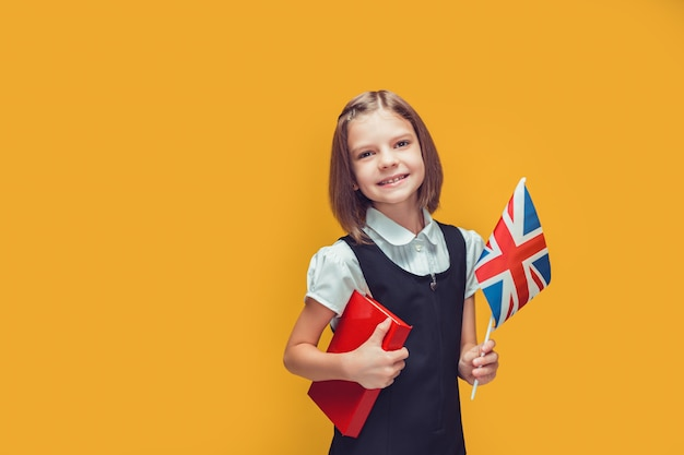 Little schoolgirl holding united kingdom flag and book studying english on yellow background