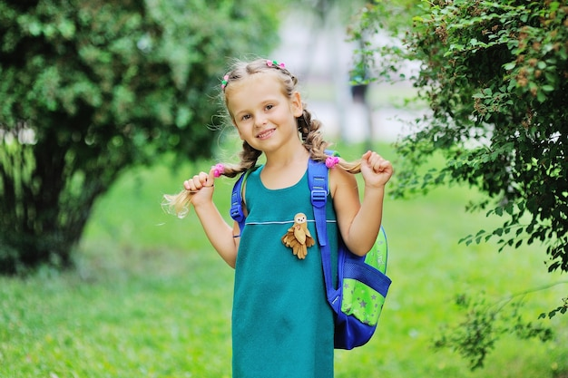 Маленькая школьница в зеленом платье со школьной сумкой улыбается на фоне зеленого ...