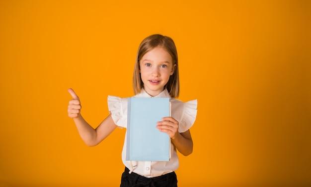 흰 블라우스를 입은 어린 여학생이 파란색 공책을 들고 노란색 배경에 손을 대고 교실을 보여줍니다.