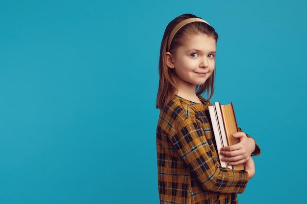 Маленькая школьница в повседневном платье держит книги на синем фоне