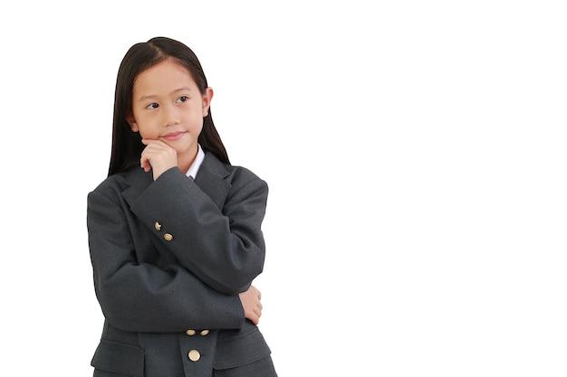정장 셔츠를 입은 작은 여학생, 비즈니스 정장을 생각하고 옆으로 바라보면서 턱을 만지고