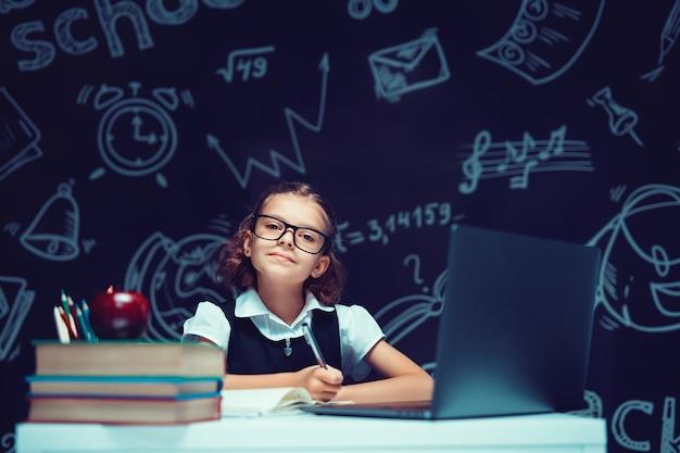学校に戻ってコンピュータ学校の黒板の背景で勉強している眼鏡の小さな女子高生