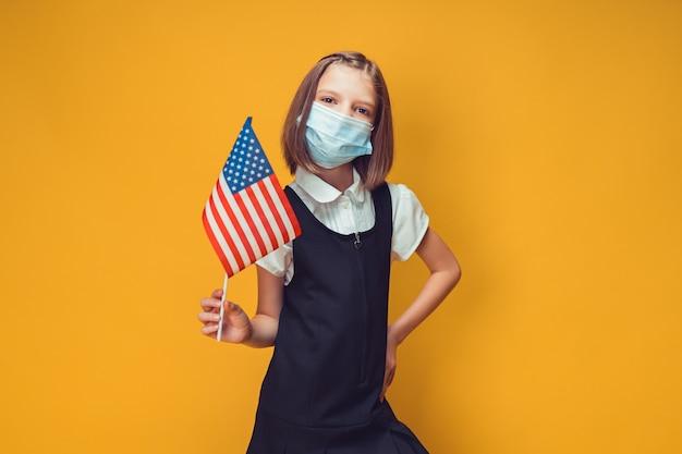 독립 기념일 안전 개념에 미국 국기가 달린 의료 마스크를 쓴 어린 여학생