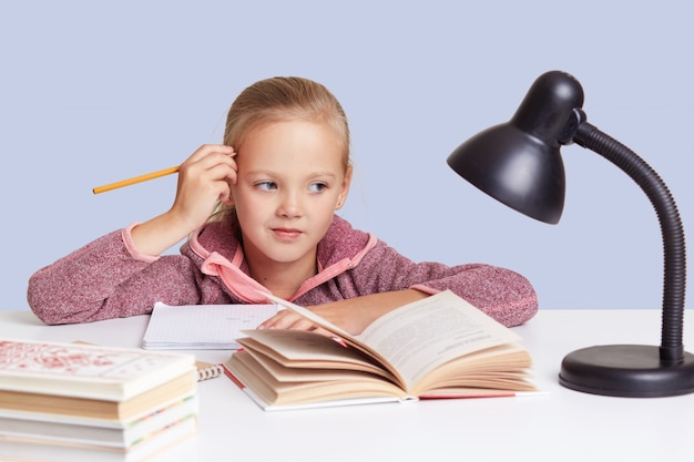 Little schoolgirl keeps hand near head, looks with thoughtful expression, thinks about homework task, uses reading lamp. children, education and schooling concept.