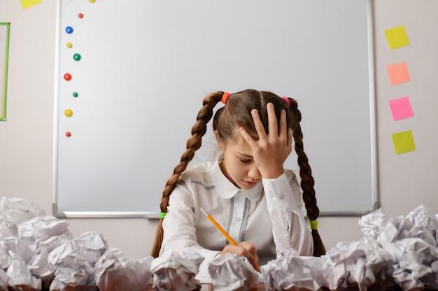 아이디어를 열심히 브레인스토밍하는 어린 여학생 학습자는 무엇에 대해 써야 할지 모릅니다