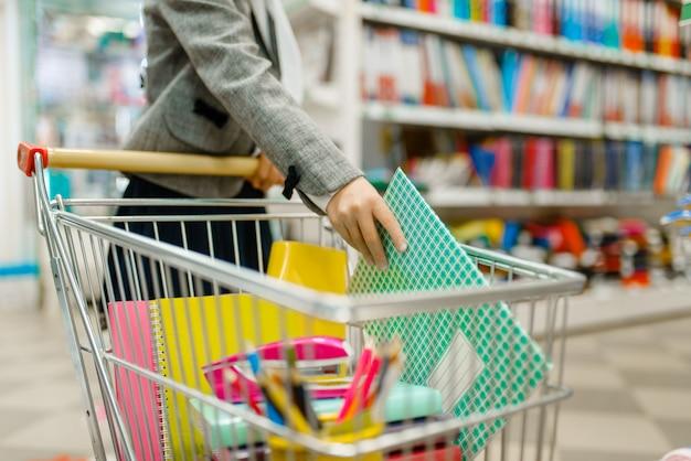 어린 여학생이 문구점 선반에있는 카트에 노트북을 넣습니다. 가게에서 사무용품을 사는 여자 아이, 슈퍼마켓에서 초등학생