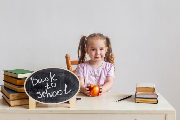 Маленькая школьница сидит за партой в школе с учебниками и держит яблоко