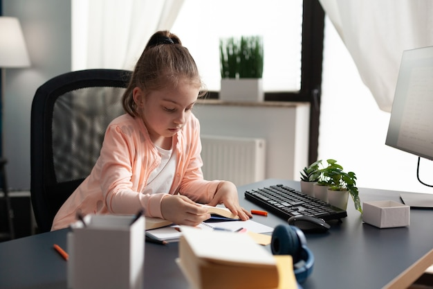 Маленькая школьница делает заметки и пишет на домашнем столе