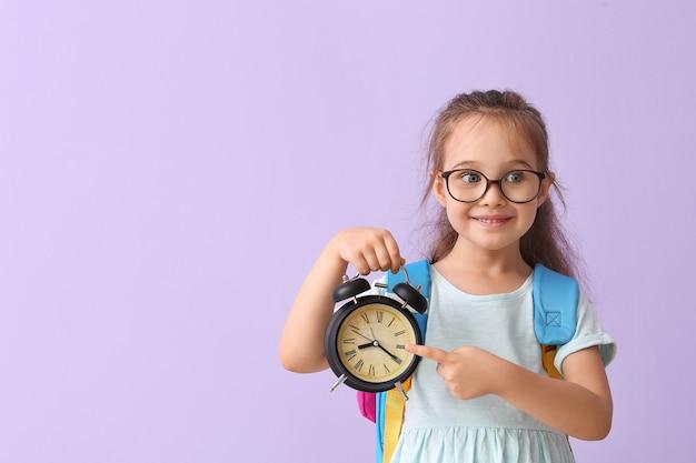 알람 시계와 함께 작은여 학생. 공부할 시간