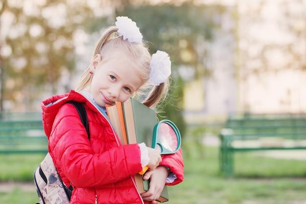 Маленькая школьница с книгами в красной куртке на фоне школы