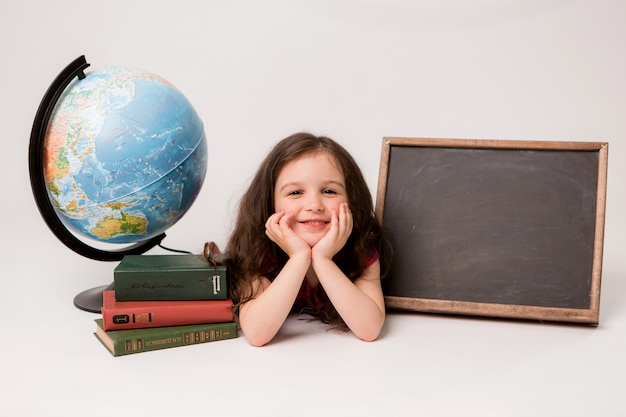 Little schoolgirl with books on a light background
