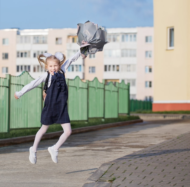 Маленькая школьница с букетом идет в школу в солнечный день