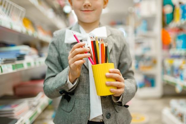 カラフルな鉛筆を持つ小さな女子高生、文房具店で買い物