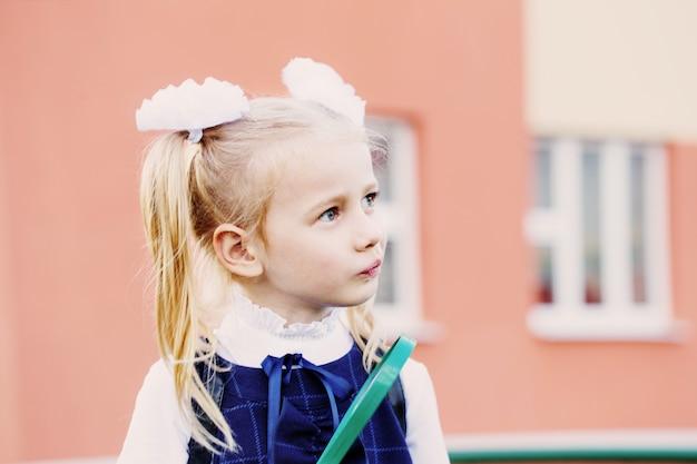 Маленькая школьница с увеличительным стеклом на открытом воздухе