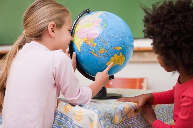 Little schoolgirls looking at a globe