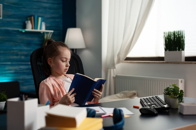 オンライン文学のレッスンのために勉強している教科書を持っている小さな小学生