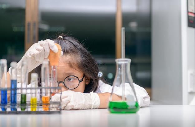Маленький ученый использует капельницу для проведения эксперимента
