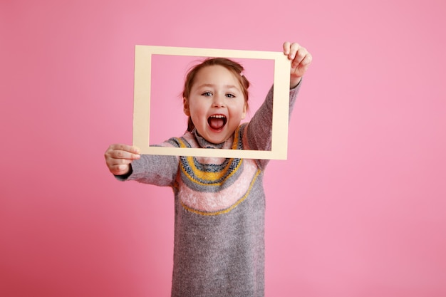 Little screaming girl in warm dress looking through frame on rosa bachground