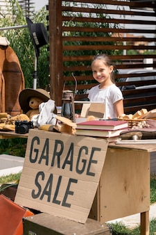 Little seller at garage sale