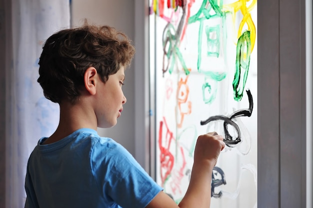 A little serious boy holds a brush in his hands and draws pictures on the window in his room