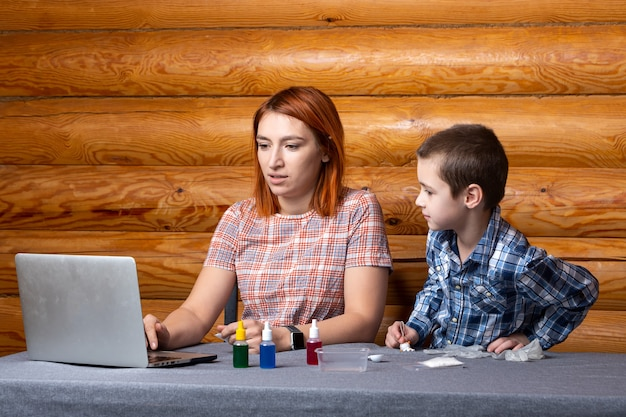 Little serious boy and mom are watching, reading instructions in a laptop and getting ready to do chemical experiments at home