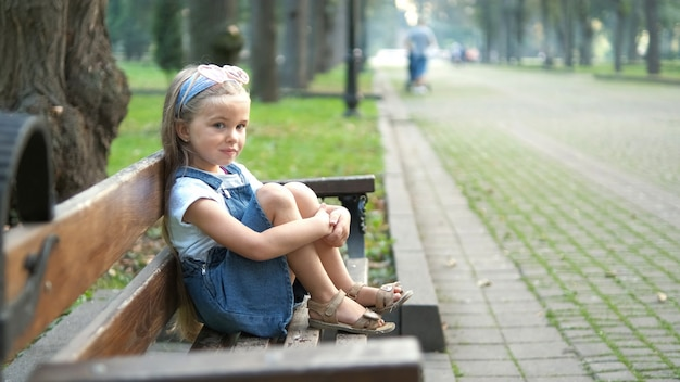 Little serious child girl sitting alone on a bench in summer park.
