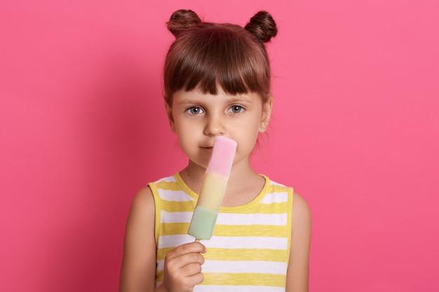 작은 심각한 소녀와 손에 과일 물 얼음을 들고 장미 벽에 흰색과 노란색 드레스에 서있는 두 재미있는 머리 롤빵이있다.